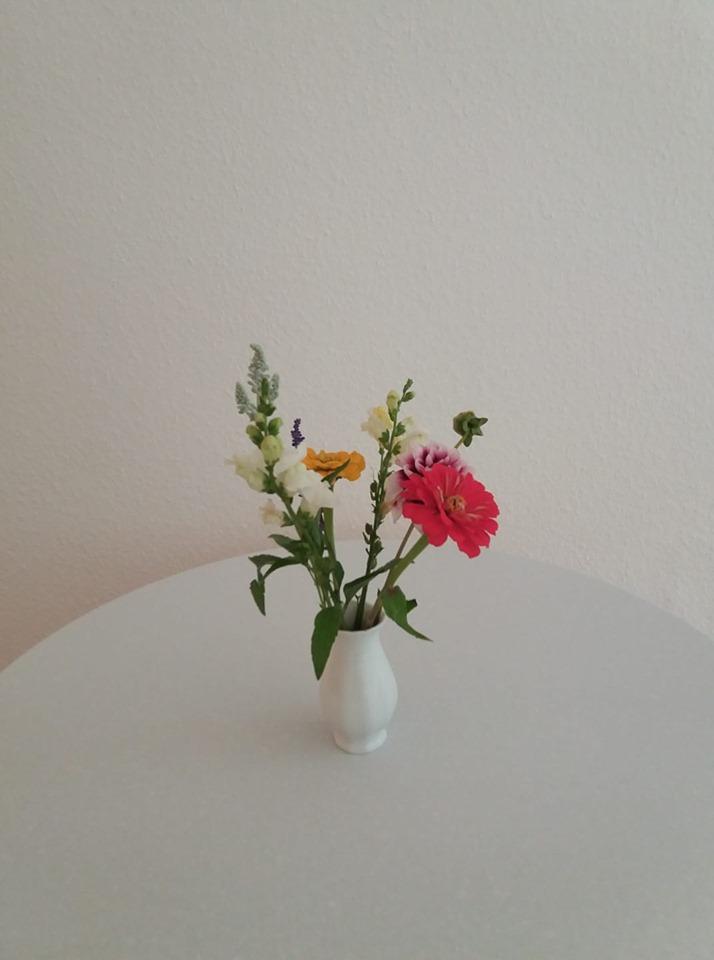 Das Bild zeigt Herbstblumen in einer Vase, die einen Moderationstisch dekorieren: ein Symbolfoto für das ausgezeichnete Feedback auf meine Arbeit.